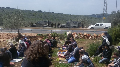 המתפללים מאזינים לדרשה - ליד החסימה של אחת הדרכים החקלאיות
