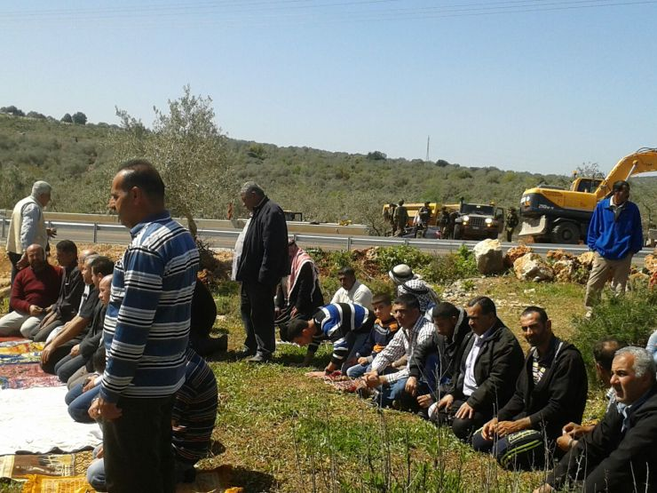 תפילת המחאה ביום ששי האחרון. ברקע אפשר לראות את החיילים ומאחוריהם שטחי המטעים שהגישה אליהם נחסמה
